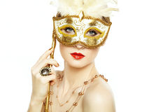 Beautiful young woman in mysterious golden Venetian mask Stock Image