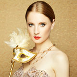 Beautiful young woman in mysterious golden Venetian mask. Fashion photo Stock Photos