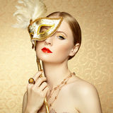 Beautiful young woman in mysterious golden Venetian mask Stock Images