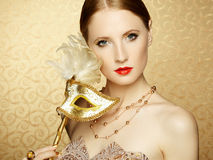 Beautiful young woman in mysterious golden Venetian mask Royalty Free Stock Photo