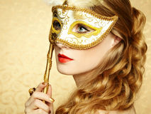 Beautiful young woman in mysterious golden Venetian mask. Fashion photo Royalty Free Stock Images