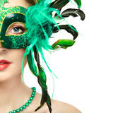 Beautiful young woman in mysterious green Venetian mask royalty free stock image