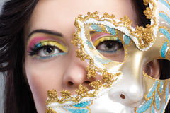 Beautiful young woman with mysterious venetian mask close up Stock Images