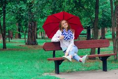 Beautiful young woman on nature benches umbrella Stock Photo