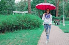 Beautiful young woman on nature park umbrella. Dripping rain Stock Photo