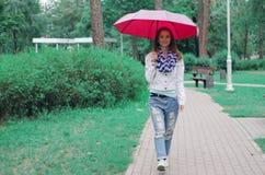 Beautiful young woman on nature park umbrella. Dripping rain Stock Image
