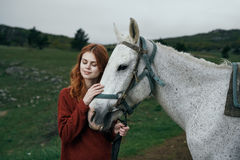 Beautiful young woman on nature walks with horse, in the mountains Stock Photos