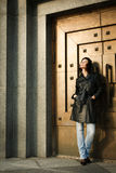 Beautiful young woman near the bronze doors Stock Photography