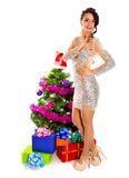 Beautiful young woman near a Christmas tree with many gifts Royalty Free Stock Images