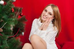 Beautiful young woman  near Christmas tree. On red background Royalty Free Stock Photography