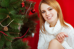 Beautiful young woman  near Christmas tree. On red background Royalty Free Stock Images