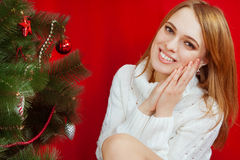 Beautiful young woman  near Christmas tree. On red background Stock Photos