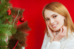 Beautiful young woman  near Christmas tree. On red background Stock Images