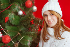 Beautiful young woman  near Christmas tree. On red background. In white knitted cap and sweater Stock Image