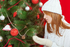 Beautiful young woman  near Christmas tree. On red background. In white knitted cap and sweater Royalty Free Stock Images
