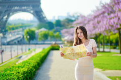 Beautiful young woman near the Eiffel tower in Paris, looking at the city map Royalty Free Stock Image