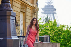 Beautiful young woman near the Eiffel tower in Paris Stock Images