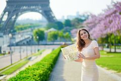 Beautiful young woman near the Eiffel tower. Beautiful young woman on Trocadero view point near the Eiffel tower in Paris, looking at the city map Royalty Free Stock Photography