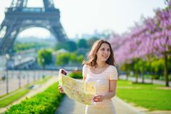 Beautiful young woman near the Eiffel tower. Beautiful young woman on Trocadero view point near the Eiffel tower in Paris, looking at the city map Stock Photo
