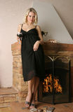 Beautiful young woman near a fireplace . Beautiful adult young woman near a fireplace Stock Images
