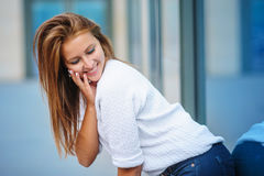 Beautiful young woman near the glass office building.  Stock Photography
