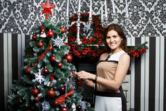 Beautiful young woman near holiday Christmas tree Stock Images