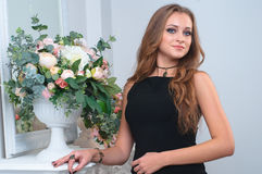 Beautiful young woman near the mirror at white room interior Royalty Free Stock Photography