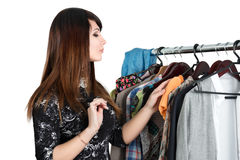 Beautiful young woman near rack with clothes Royalty Free Stock Photos