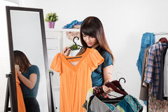 Beautiful young woman near rack with clothes Stock Photo