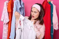 Beautiful young woman near rack with hangers. Shocked lady finds awful stain on white blouse. Brunette female holds shirt. Girl. Goes shopping. Girl wears royalty free stock photography