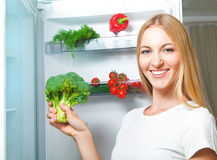 Beautiful young woman near refrigerator Royalty Free Stock Photography