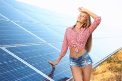 Beautiful young woman near solar panels. Outdoors Royalty Free Stock Photos
