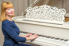 Beautiful young woman near a white grand piano. The concept of musical education, creative development of personality royalty free stock photography