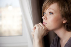 Beautiful young woman near the window Stock Photos