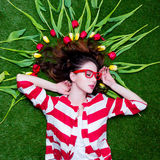 Beautiful young woman near yellow and red tulips  lying on the w. Onderful green grass background Royalty Free Stock Photo