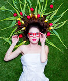 Beautiful young woman near yellow and red tulips  lying on the w. Onderful green grass background Stock Photography