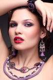Beautiful young woman in necklace. Portrait of beautiful young brunette woman in necklace and earrings on dark gray background Stock Photography