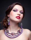 Beautiful young woman in necklace. Portrait of beautiful young brunette woman in necklace and earrings on dark gray background Royalty Free Stock Photos