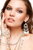 Beautiful young woman in necklace. Portrait of beautiful young brunette woman in and earrings  touching her face Royalty Free Stock Photo