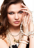 Beautiful young woman in necklace. Portrait of beautiful young brunette woman in and earrings  touching her face Stock Image