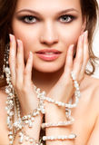 Beautiful young woman in necklace. Portrait of beautiful young brunette woman in and earrings  touching her face Stock Photos