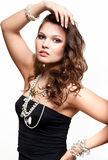 Beautiful young woman in necklace. Portrait of beautiful young brunette woman in and earrings on white background Royalty Free Stock Photography