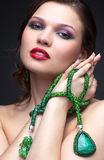 Beautiful young woman in necklace. Portrait of beautiful young brunette woman in malachite necklace, pendent, and earrings on dark gray background Stock Images