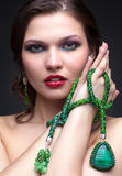 Beautiful young woman in necklace. Portrait of beautiful young brunette woman in malachite necklace, pendent, and earrings on dark gray background Royalty Free Stock Photo