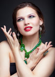 Beautiful young woman in necklace. Portrait of beautiful young brunette woman in malachite necklace, pendent, ring and earrings on dark gray background Stock Photo
