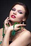 Beautiful young woman in necklace. Portrait of beautiful young brunette woman in malachite necklace, pendent, ring and earrings on dark gray background Stock Photos