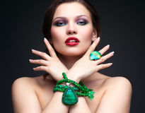Beautiful young woman in necklace. Portrait of beautiful young brunette woman in malachite necklace, pendent, ring and earrings on dark gray background Royalty Free Stock Photography