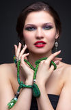 Beautiful young woman in necklace. Portrait of beautiful young brunette woman in malachite necklace, pendent, ring and earrings on dark gray background Royalty Free Stock Photo