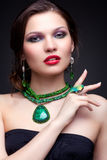 Beautiful young woman in necklace. Portrait of beautiful young brunette woman in malachite necklace, pendent, ring and earrings on dark gray background Royalty Free Stock Photos