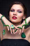 Beautiful young woman in necklace. Portrait of beautiful young brunette woman in malachite necklace, pendent, ring and earrings on dark gray background Stock Image